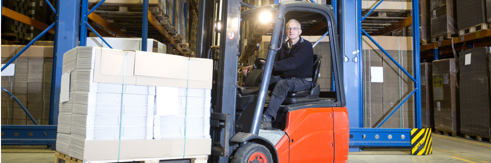 driver posing in front of a row with storage racks